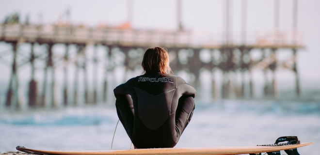 Surfista frente al mar al atardecer