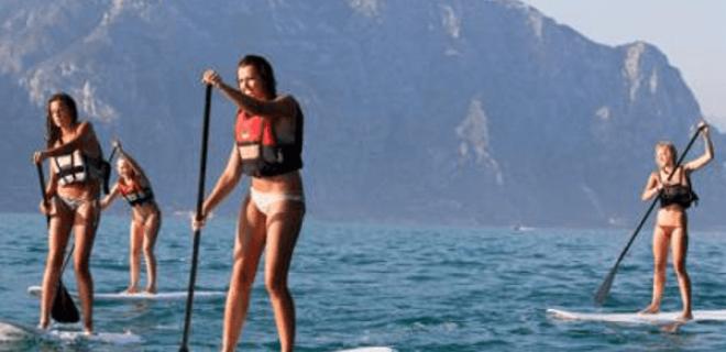 4 bellas jóvenes hacen Stand Up Paddle Surf (SUP) en un tranquilo mar sin olas