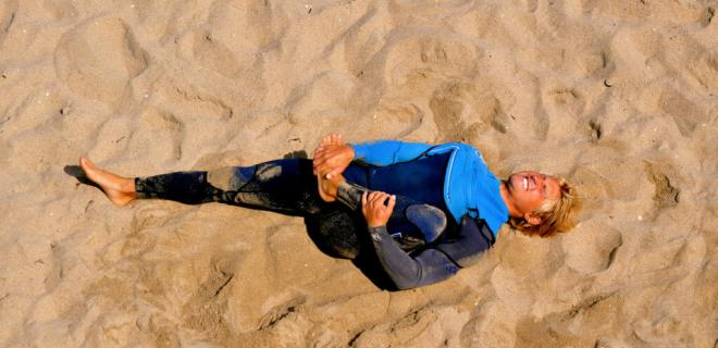 Surfer stretching at Huntington Beach (California)