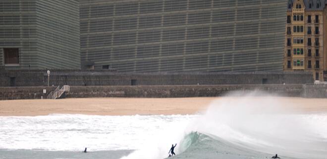 Surfistas en la playa de Zurriola con el emblemático Kursaal al fondo (Donosti, Euskadi)