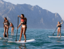 4 bellas jóvenes hacen Stand Up Paddle Surf (SUP) en un tranquilo mar sin olas