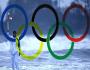 Surfista surfeando con llama olímpica